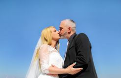 The happy handsome wedding couple are standing and kissing. stock photography