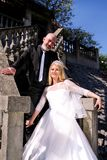 The happy handsome wedding couple are standing steps in front of house. stock photos