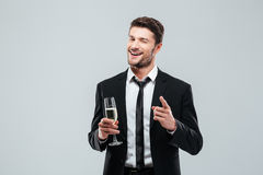 Happy handsome young businessman drinking champagne and pointing on you. Over white background Royalty Free Stock Images