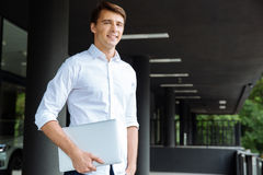 Happy handsome young businessman standing and holding laptop Stock Photo