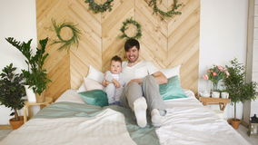 Happy handsome young father lying on bed and playing with his son stock footage