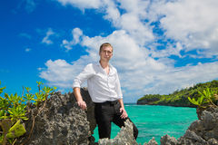 Happy handsome young male wearing in white shirt is standing on. The tropical beach under the sun on sunny summer day during holidays vacation Stock Photos