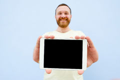Happy Handsome young man with a beard showing something on a tablet  on a blue background, close-up for your text Stock Photo