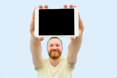 Happy Handsome young man with a beard showing something on a tablet  on a blue background, close-up for your text Stock Images