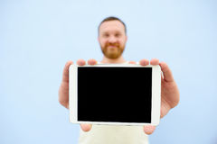 Happy Handsome young man with a beard showing something on a tablet  on a blue background, close-up for your text Stock Photos