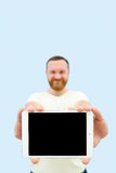 Happy Handsome young man with a beard showing something on a tablet  on a blue background, close-up for your text Stock Image
