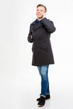 Happy handsome young man in coat talking on mobile phone Royalty Free Stock Images