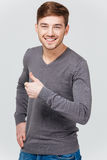 Happy handsome young man in grey pullover showing thumbs up. Over white background Stock Photography