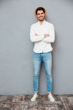 Happy handsome young man in hat standing with arms crossed Royalty Free Stock Images