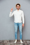 Happy handsome young man in hat standing and pointing up Royalty Free Stock Image
