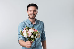 Happy handsome young man holding a bunch of flowers. Stock Images