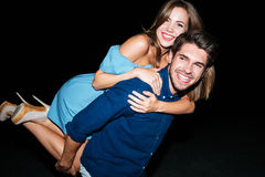 Happy handsome young man holding girlfriend on his back. Happy handsome young men holding girlfriend on his back at night stock images