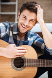 Happy handsome young man holding guitar Stock Images
