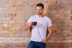 Happy man with mug. A happy handsome young man holding a mug in a white tshirt Royalty Free Stock Photo