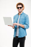 Happy handsome young man holding and using laptop Royalty Free Stock Photos