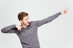 Happy handsome young man pointing away with both hands Royalty Free Stock Images