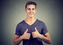 Happy handsome young man showing thumbs up stock photo