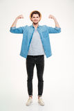 Happy handsome young man standing and showing biceps Royalty Free Stock Images