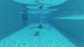 Happy handsome young man in the swimming pool, underwater view. Vacation summer time. Action camera. Happy handsome young man swimming in the swimming pool stock footage
