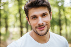 Happy handsome young man wearing white t-shirt in forest Stock Image