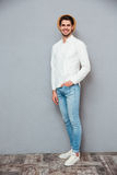 Happy handsome young man in white shirt, jeans and hat Royalty Free Stock Photo