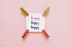 `Happy` handwritten with watercolor in calligraphy style, miniature clothespins. Flat lay Stock Photo