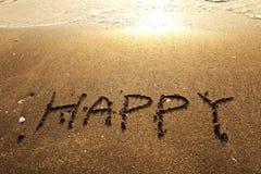 Happy handwritten words on sand Stock Photo