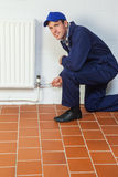 Happy handyman in blue coveralls repairing a radiator Stock Photography