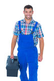 Happy handyman in coveralls carrying toolbox Royalty Free Stock Photos