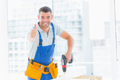 Happy handyman drilling hole in plank while gesturing thumbs up Stock Photo
