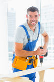 Happy handyman drilling plank in office Stock Photos