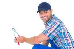 Happy handyman holding pliers on white background Royalty Free Stock Image