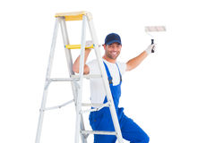 Happy handyman on ladder while using paint roller Royalty Free Stock Image