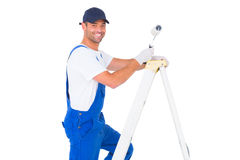 Happy handyman with paint roller climbing ladder Royalty Free Stock Images