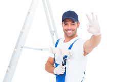 Happy handyman with paint roller gesturing okay. Portrait of happy handyman with paint roller gesturing okay on white background Royalty Free Stock Photos