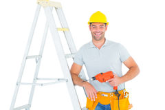 Happy handyman with power drill leaning on ladder. Portrait of happy handyman with power drill leaning on ladder over white background Royalty Free Stock Photo