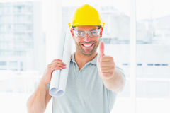 Happy handyman with rolled up blueprint gesturing thumbs up Stock Image