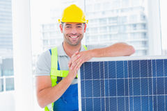 Happy handyman with solar panel in bright office Stock Photos