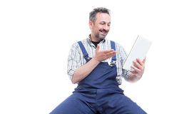 Happy handyman wathcing something funny on tablet. Happy handyman in blue overalls wathcing something funny on tablet and smiling isolated on white background stock photography