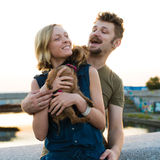 Happy hansome young couple with small dog Stock Image
