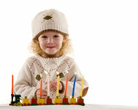 Happy Hanukkah. Young blond hair three year old boy lighting the candles in the Jewish tradition to celebrate Hanukkah stock photography
