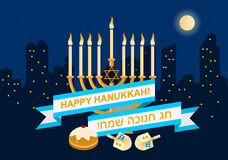 Happy Hanukkah Design. A postcard design for Hanukkah with text Happy Hanukkah in English and Hebrew, menora with burning candles and a dreidel with a night city