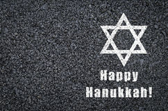 Happy Hanukkah - star of david and phrase written on asphalt background. White color stock photo