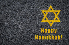 Happy Hanukkah - star of david and phrase written on asphalt background stock photography