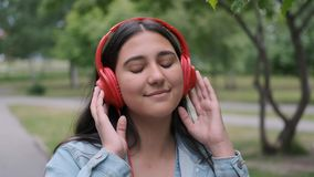 Happy girl dancing in the park near the trees listening to cheerful music in headphones. Fun mood. Close-up. Happy happy girl in denim clothes dancing in the stock video
