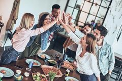 So happy!. Top view of young people giving each other high-five in a symbol of unity and smiling while having a dinner party indoors royalty free stock image