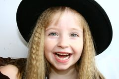 Happy hat girl. Young girl having fun trying on hats Royalty Free Stock Photos