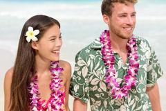 Happy Hawaii beach couple in Aloha Hawaiian shirt. Portrait of Asian women and Caucasian men on beach walking with flower leis and typical attire for their Stock Image