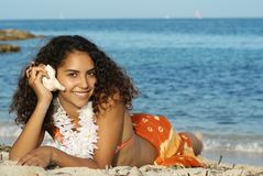 Happy hawaiian girl. Young girl listening to the sea with a shell with perfect teeth,skin,hair and tan Stock Photos
