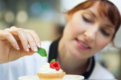 Happy head chef putting mint leaf on little cake Stock Photography